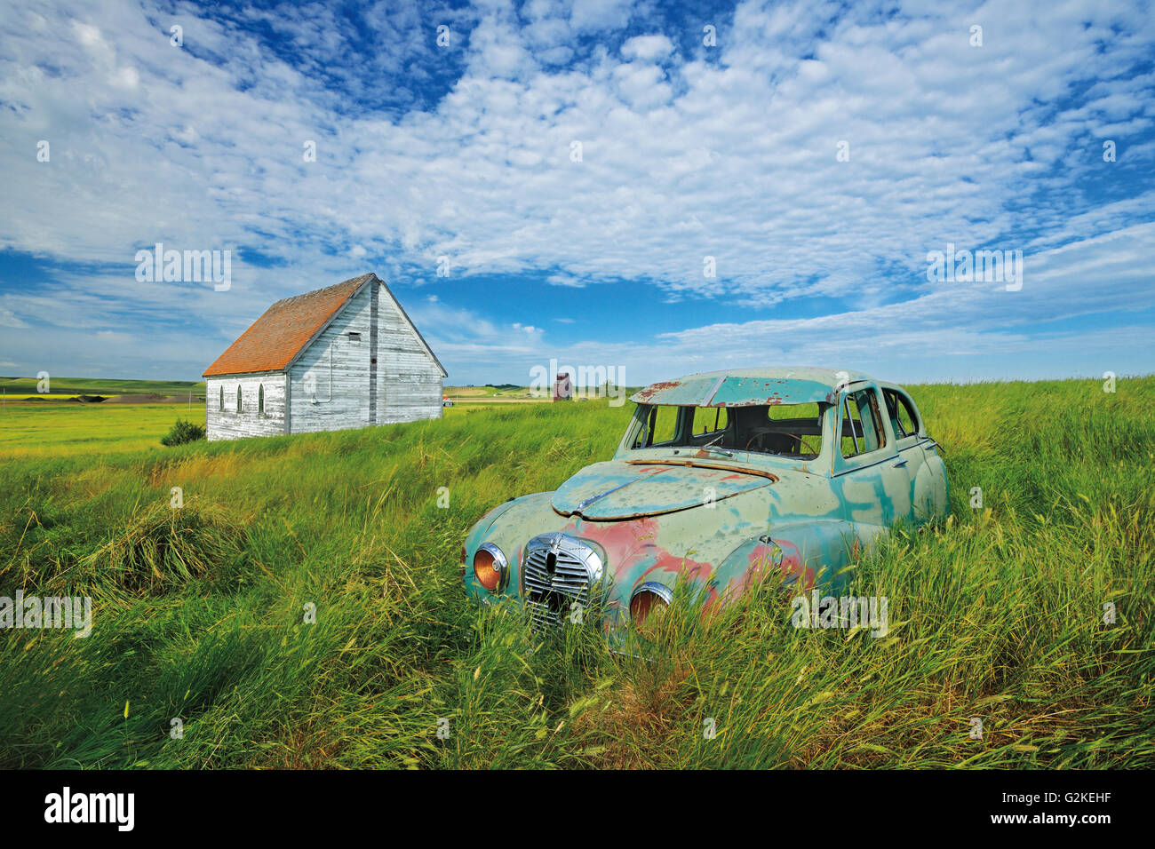 Old Austin car and church in field in ghost town  Neidpath Saskatchewan Canada - Stock Image