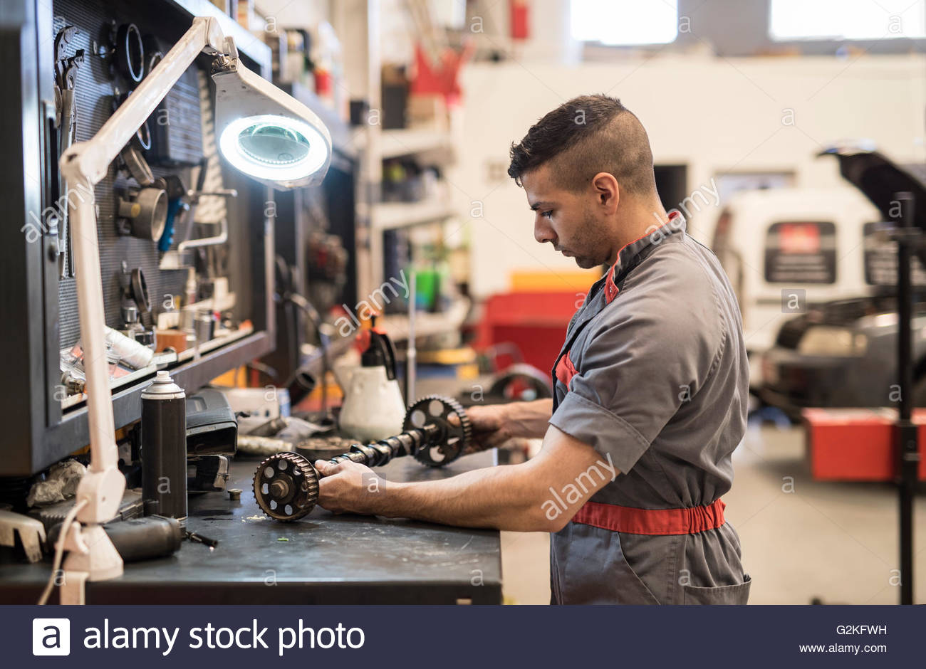 Mechanic man working in tools, table with magnify lens - Stock Image