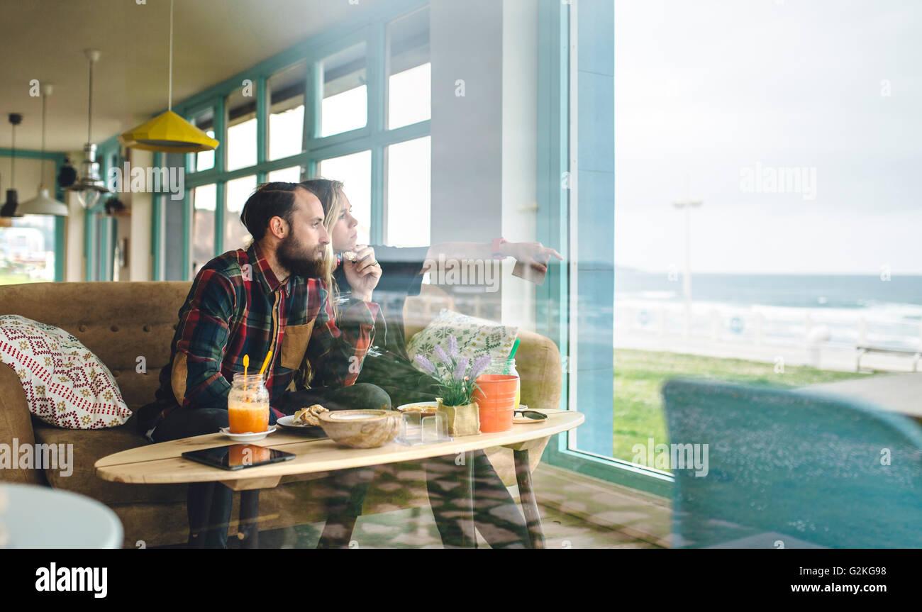 Spain, Asturias, Couple enjoying the seascape through the cafe window while having a brunch Stock Photo
