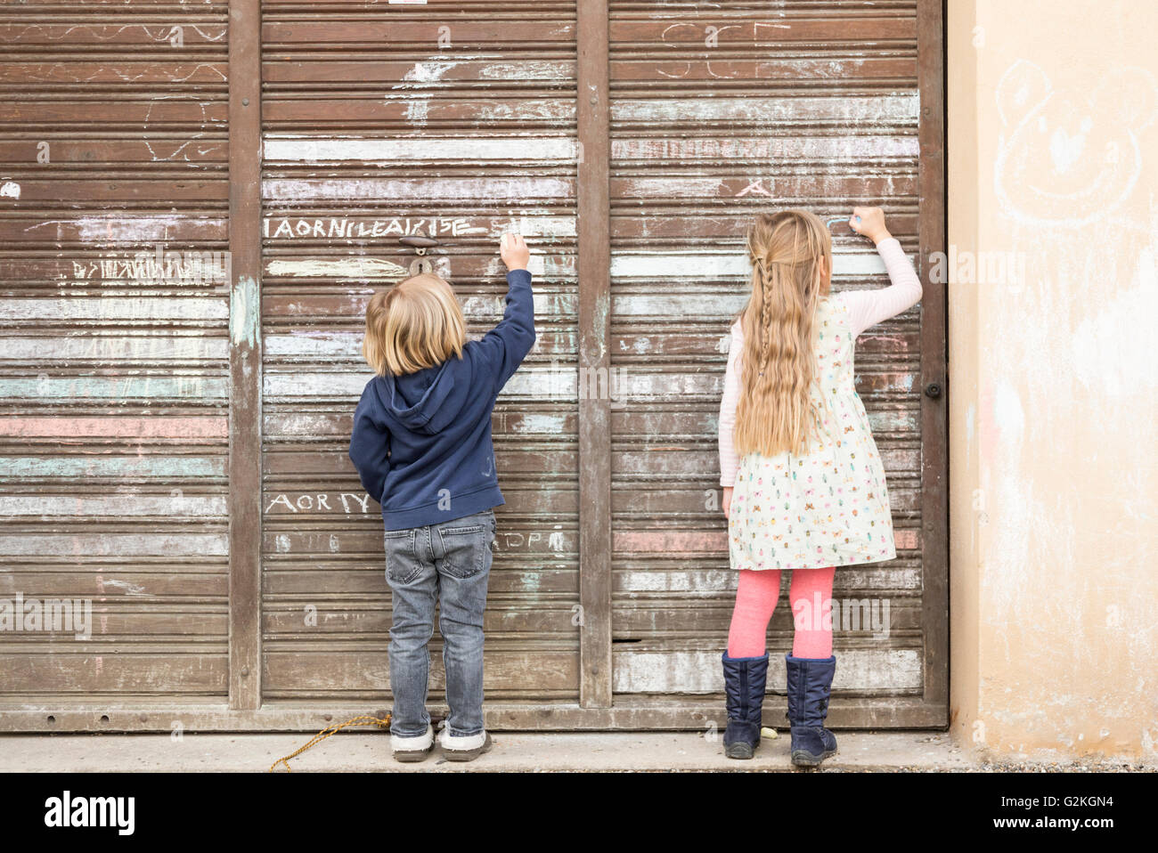 Back view of two little girls drawing on an old garage door - Stock Image