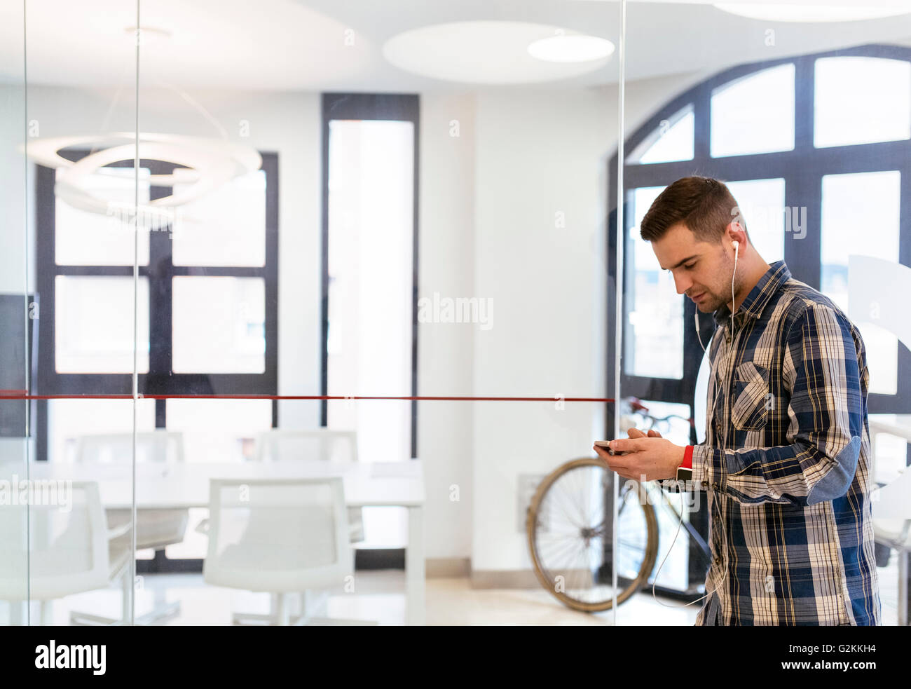 Young man wearing earbuds in office - Stock Image