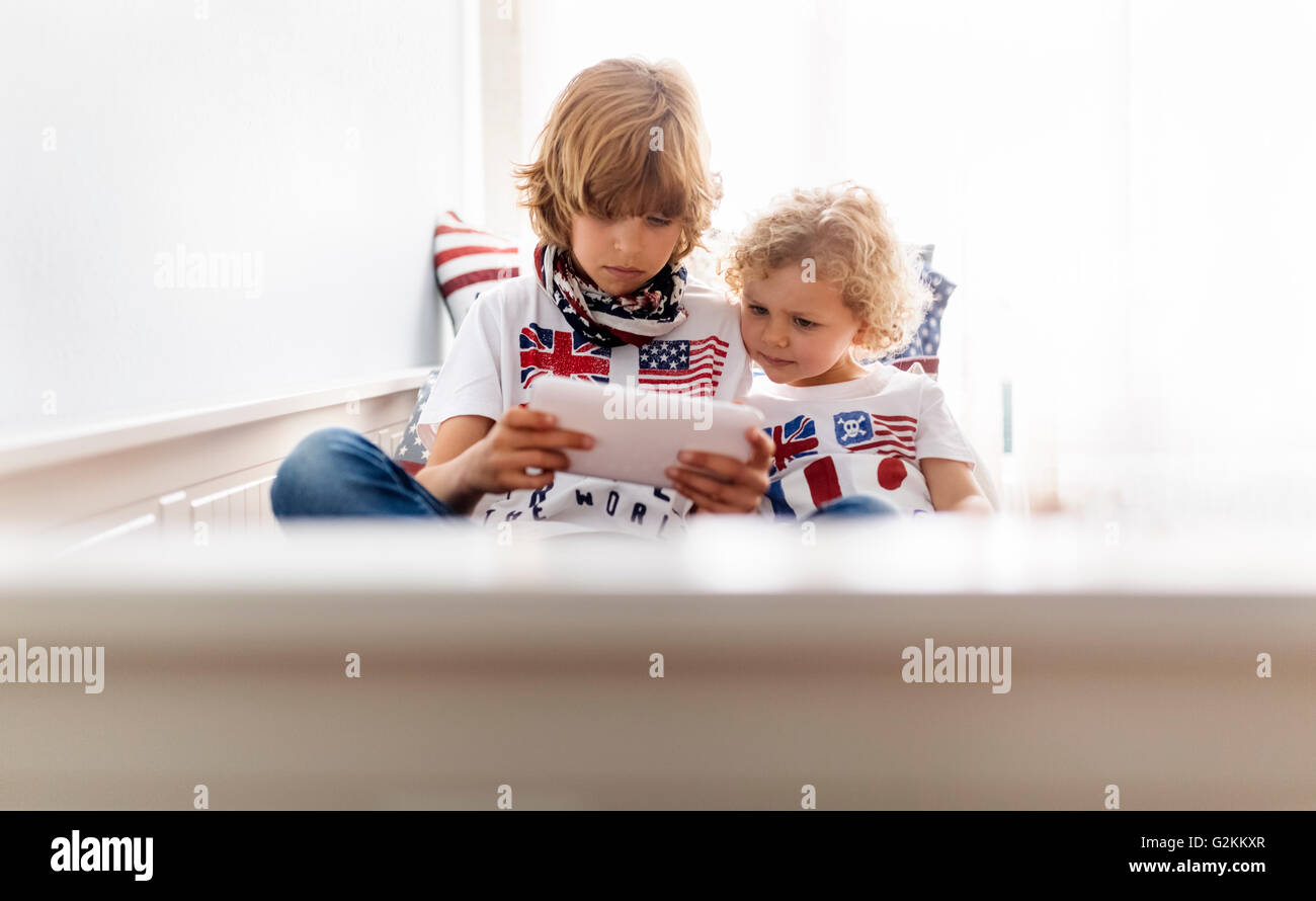 Two boys playing with digital tablet at home - Stock Image