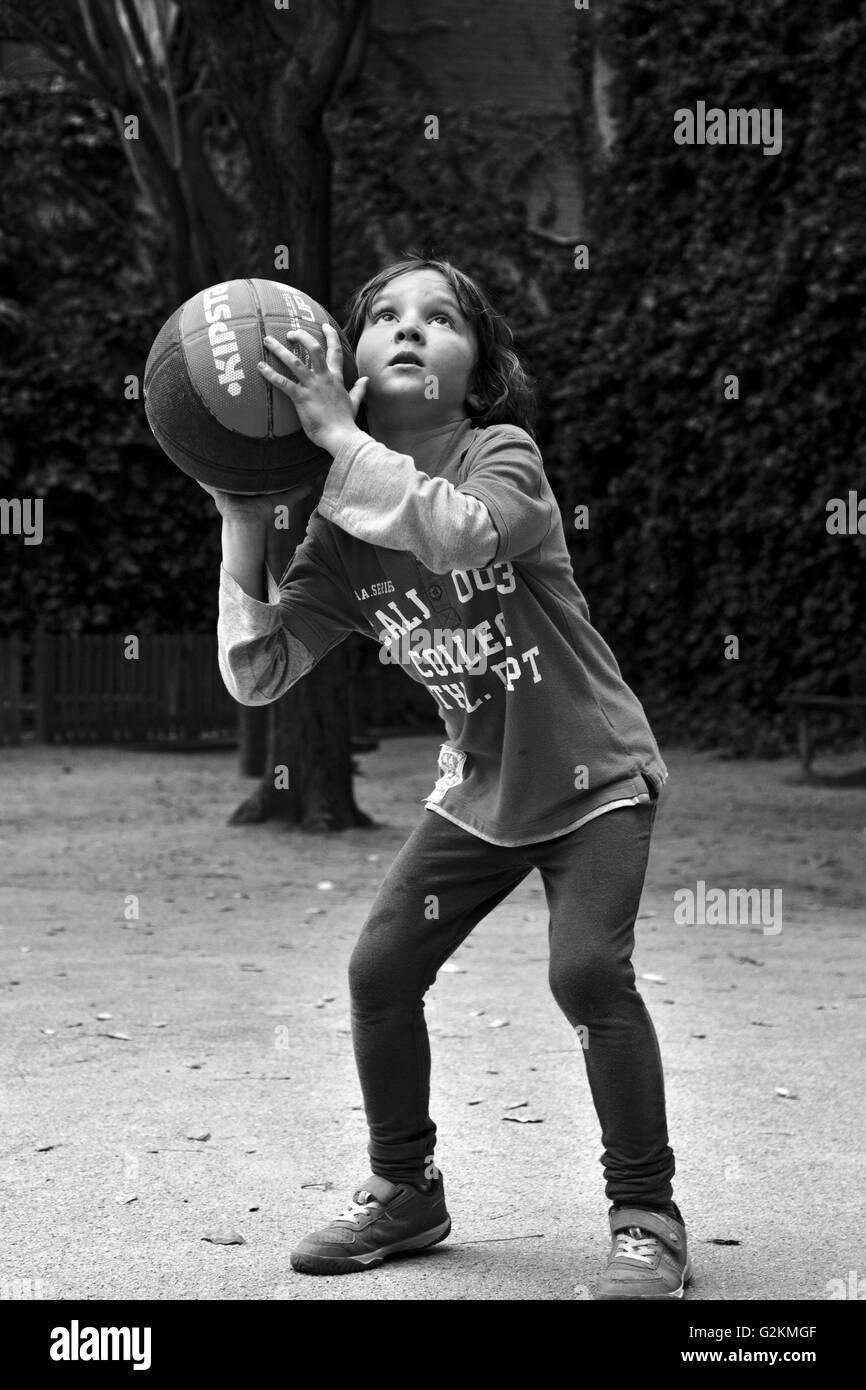 7 year old boy preparing to shoot a basket. - Stock Image