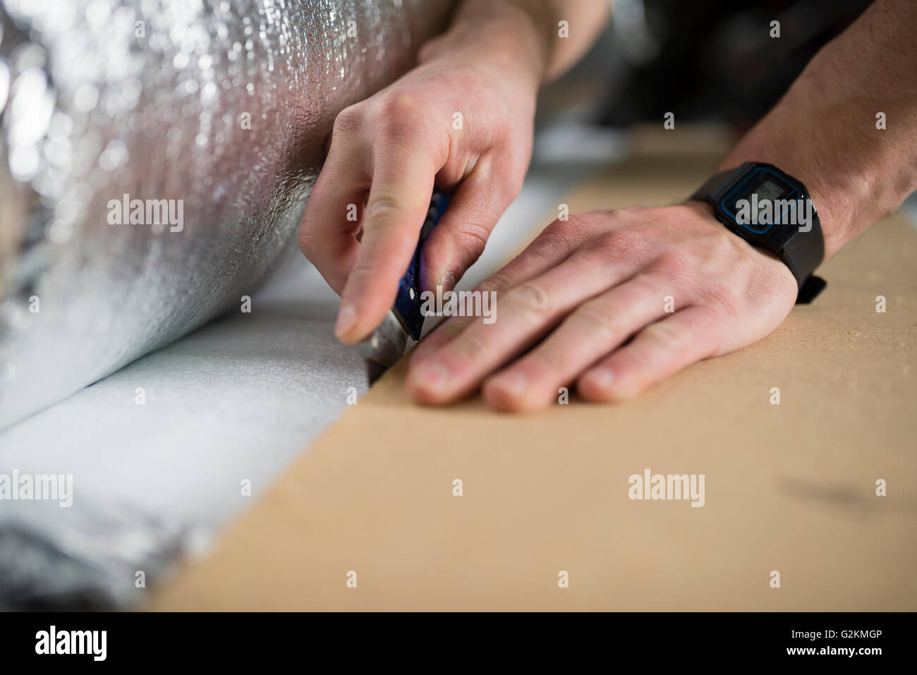Young man cutting a insulating material for a laminate-flooring - Stock Image