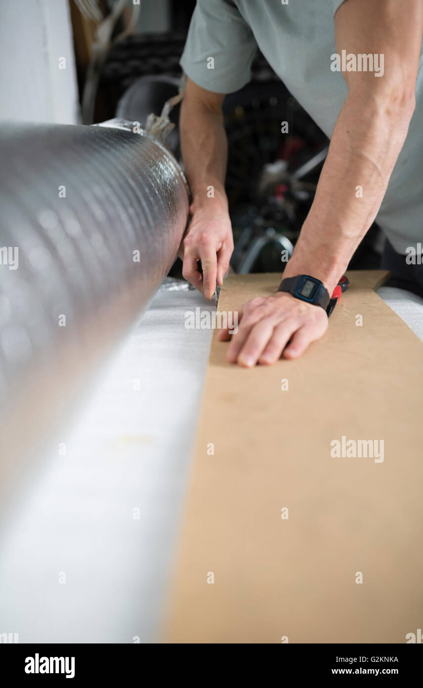 Young man cutting a insulating material for a laminate flooring - Stock Image