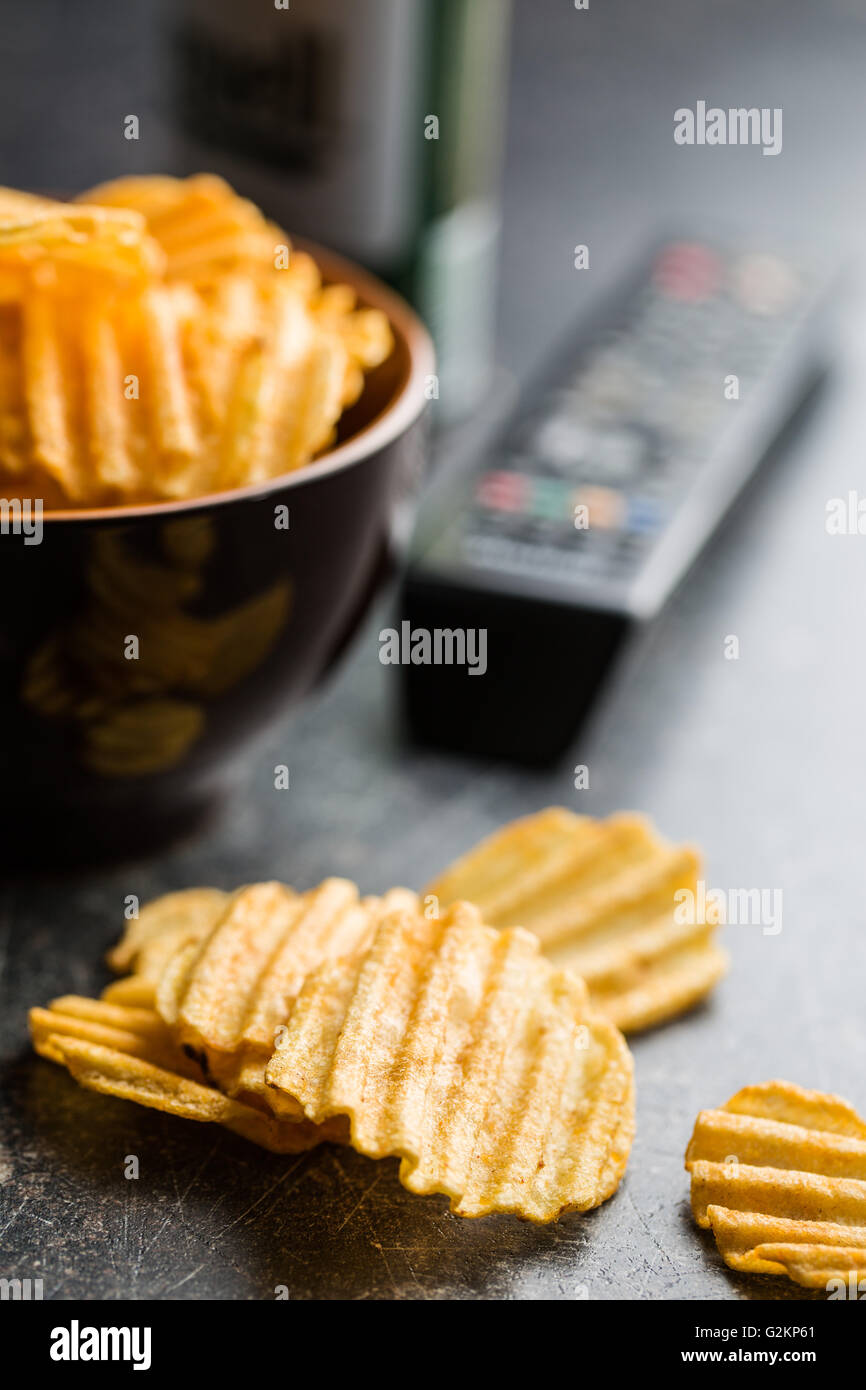 Crinkle cut potato chips on table. Tasty spicy potato chips and tv remote controller. - Stock Image