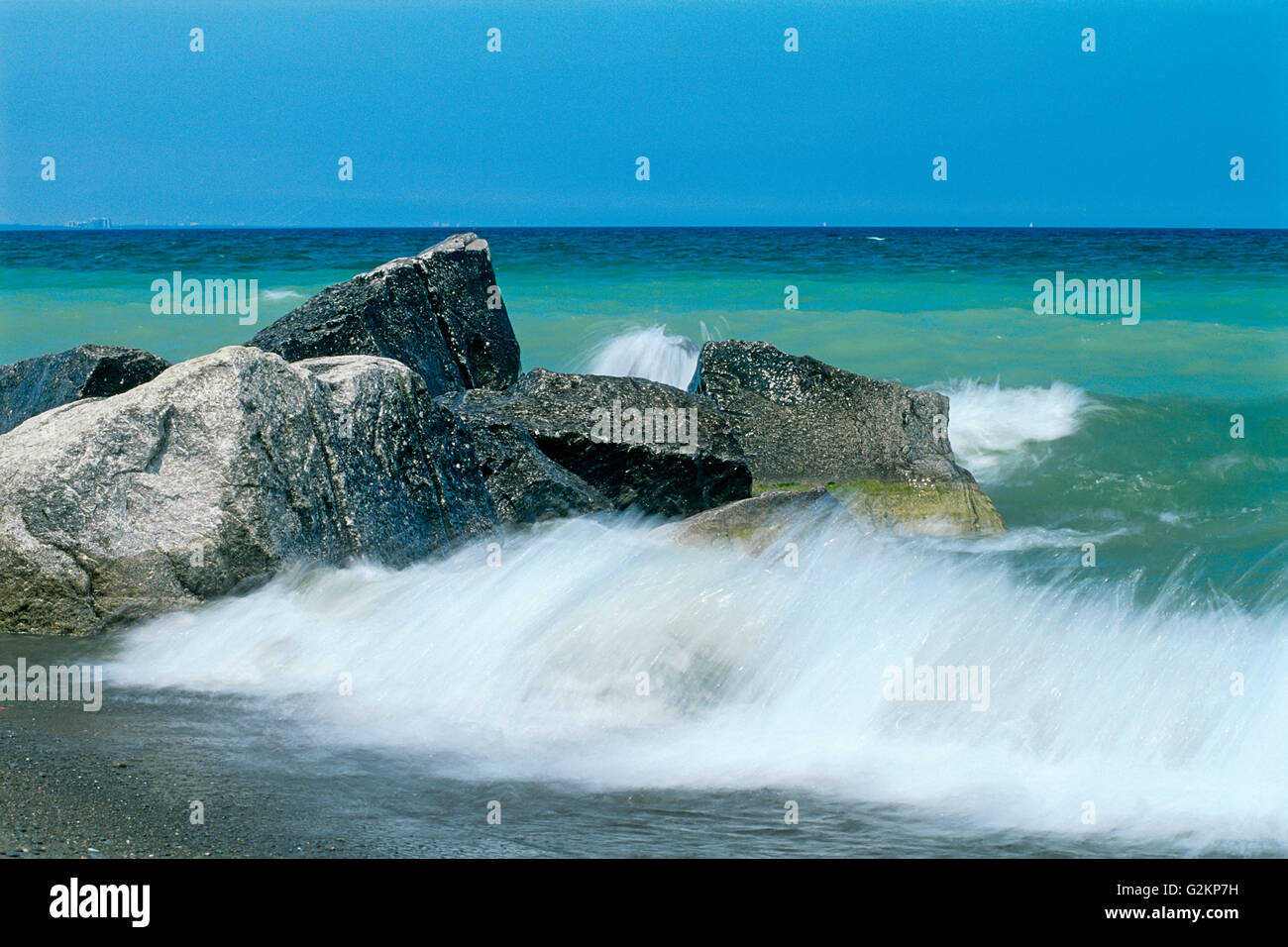 crashing waves on rocks on Lake Ontario Burlington Ontario Canada - Stock Image