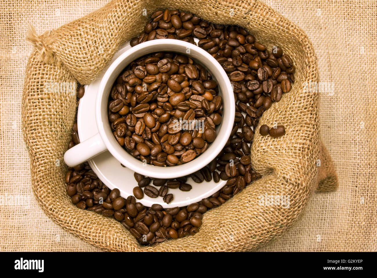 Fresh Roasted Coffee Beans In Bag And In White Coffee Cup. Shot from above - Stock Image