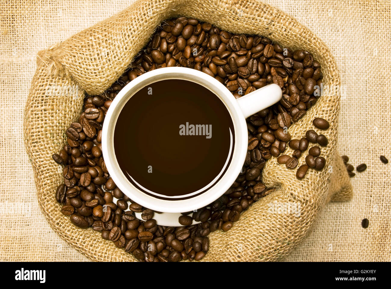 Roasted Coffee Beans In Burlap Bag With Fresh Brewed Coffee On Top - Stock Image