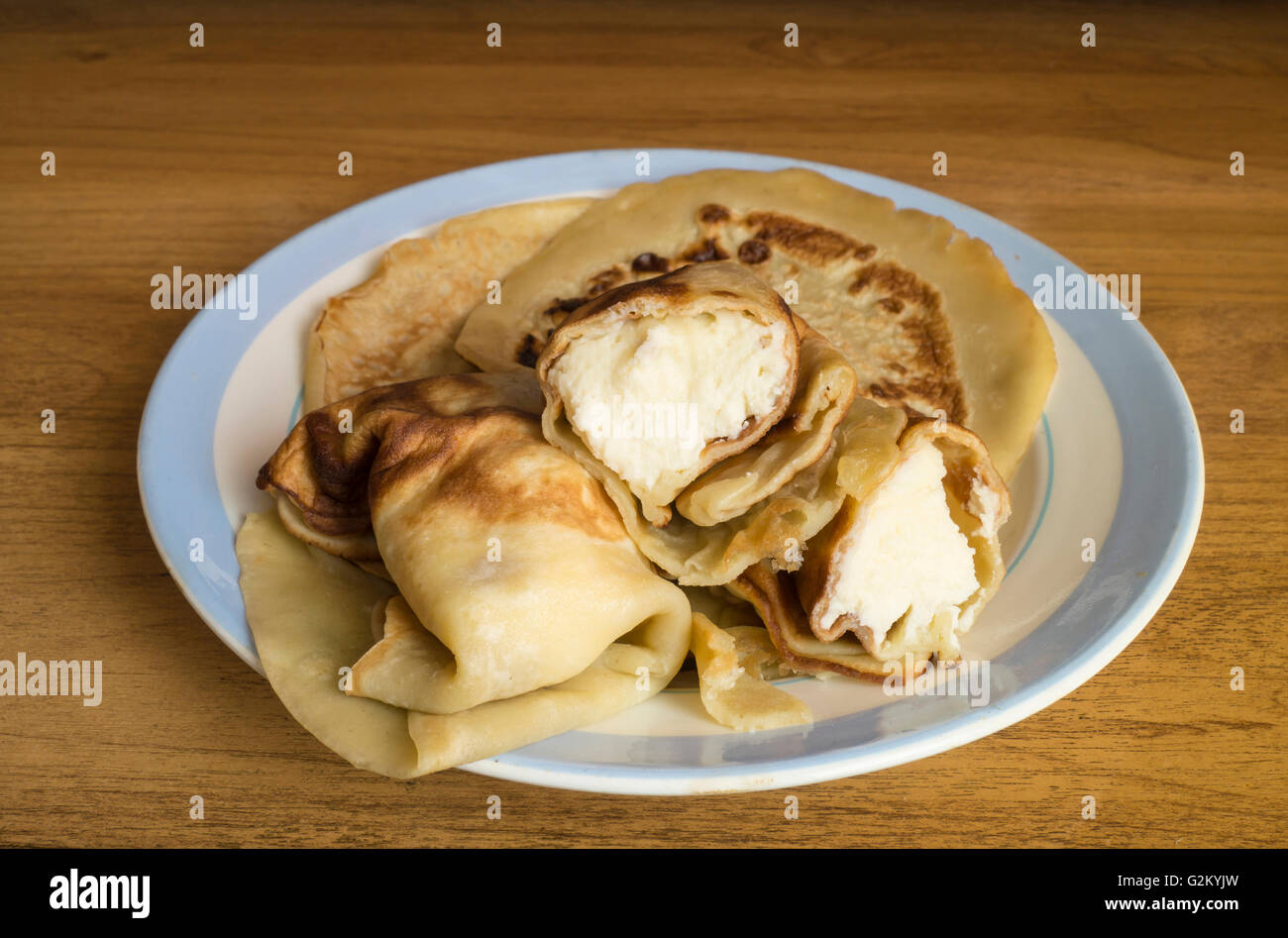 Home pancakes with white pot cheese for morning meal on blue plate - Stock Image