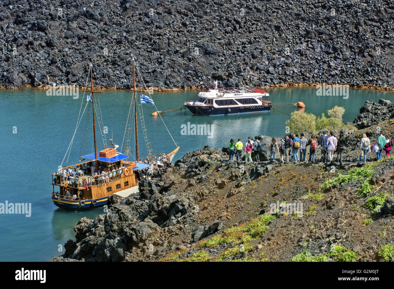 Two excursion boats and tourists at the little haven in Kameni volcanic islet, in Santorini island, Cyclades, Greece - Stock Image