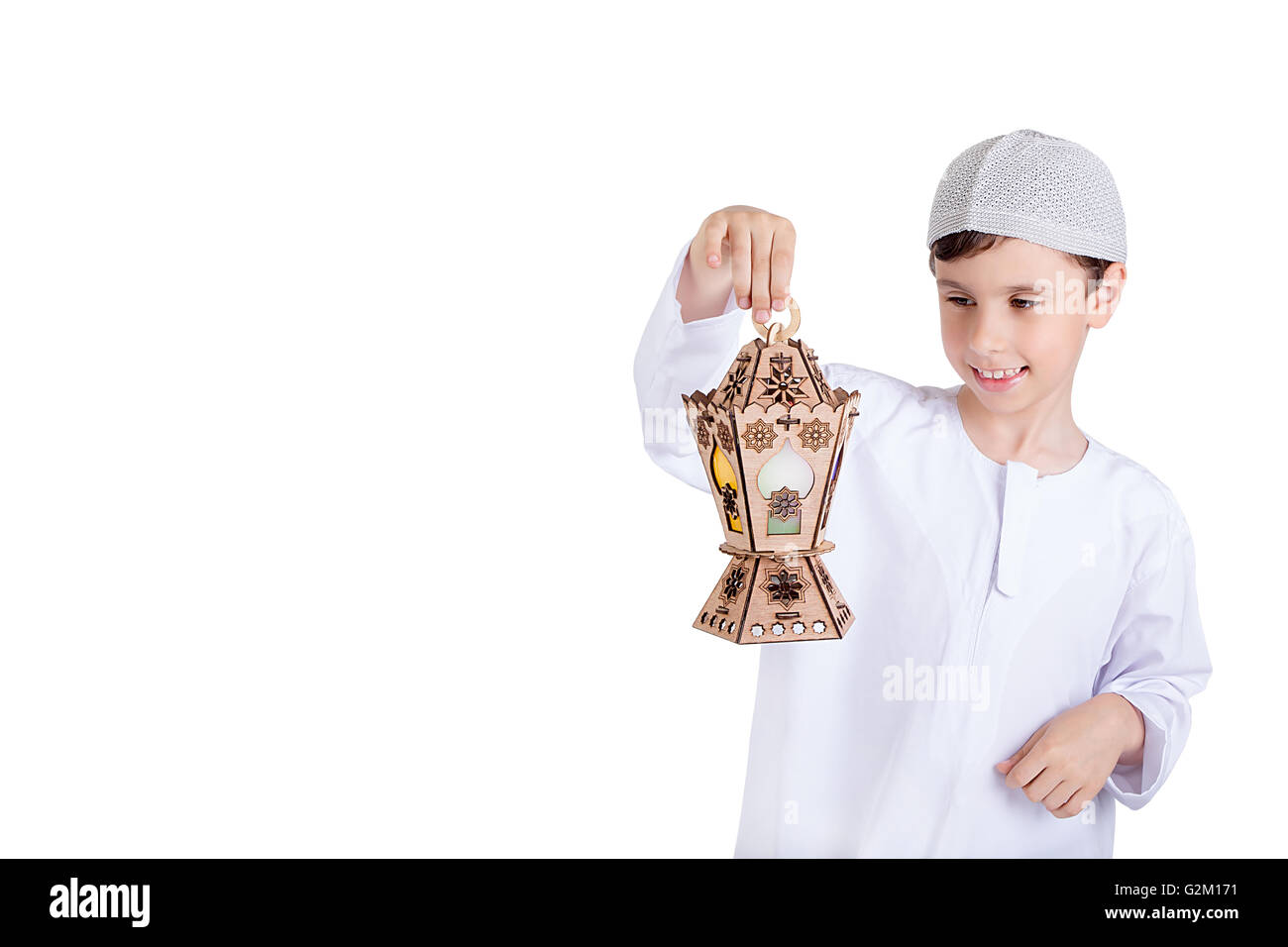 Happy young kid playing with Ramadan lantern - Stock Image