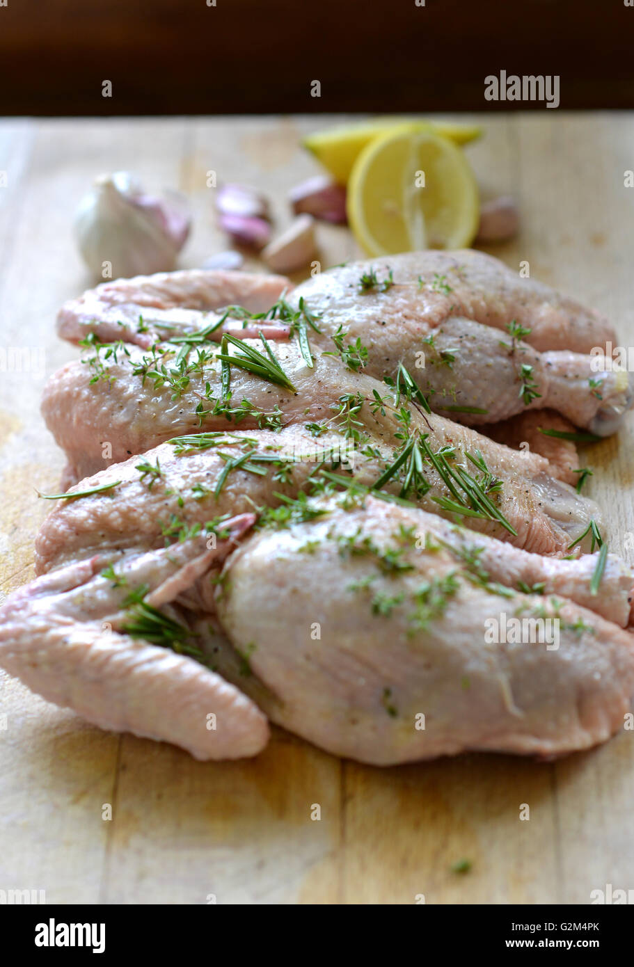 Raw spatchcock (butterfly) chicken and herbs - Stock Image