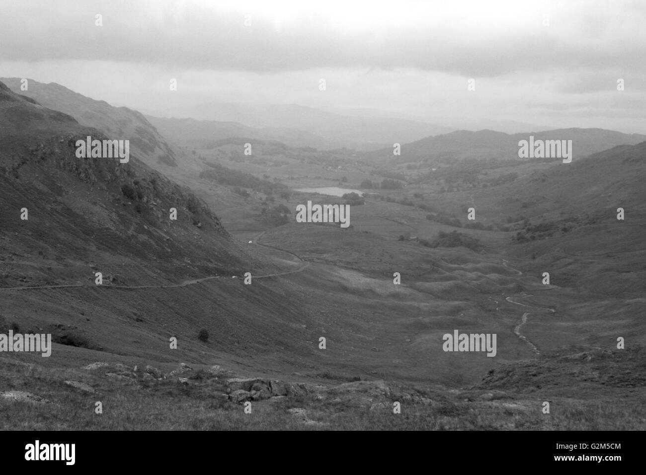 Eastern Climb over the Wrynose Pass with Little Langdale Tarn in the distance - Stock Image