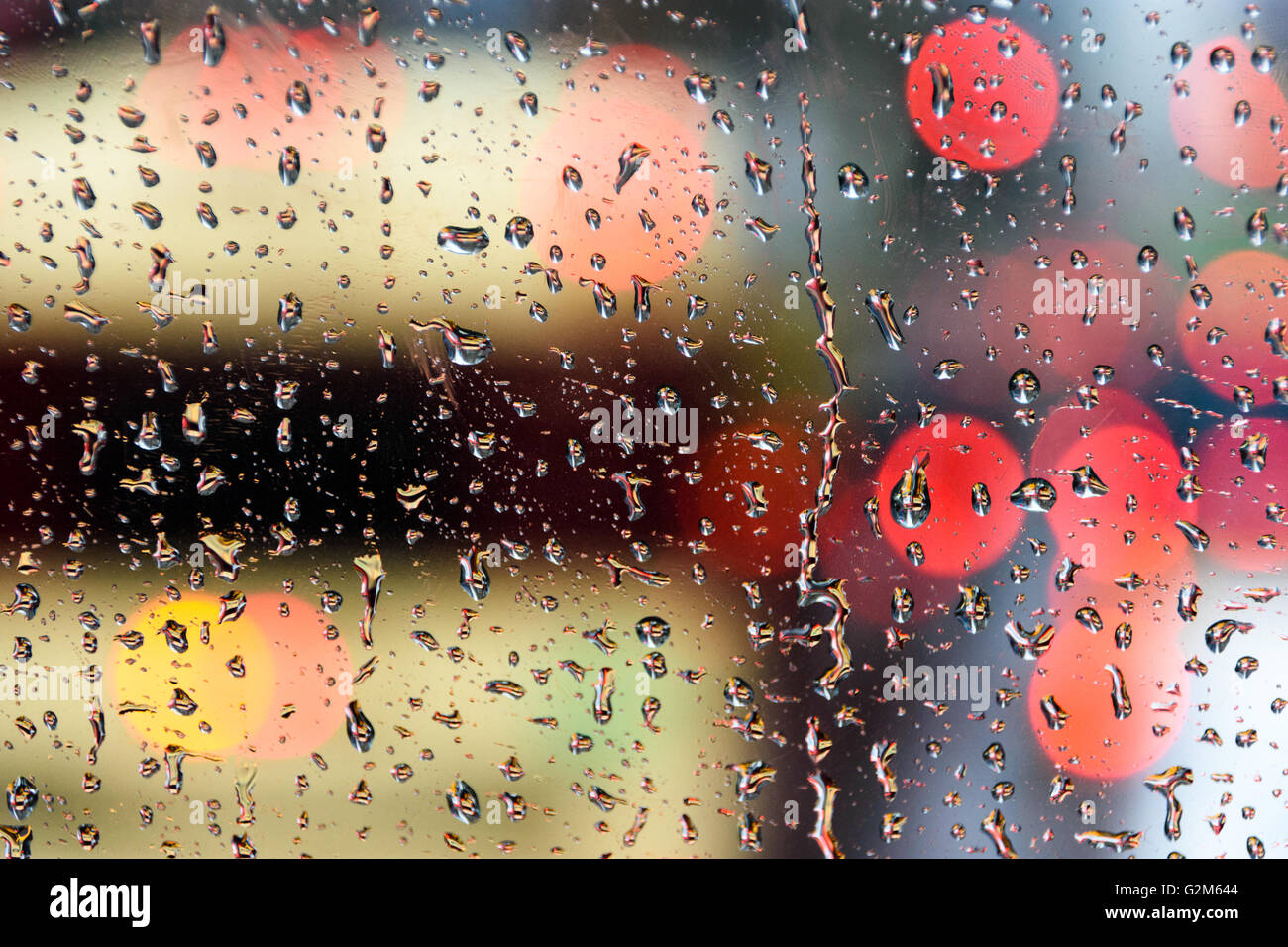 Abstract bokeh lights seen through raindrops streaking down a windscreen Stock Photo