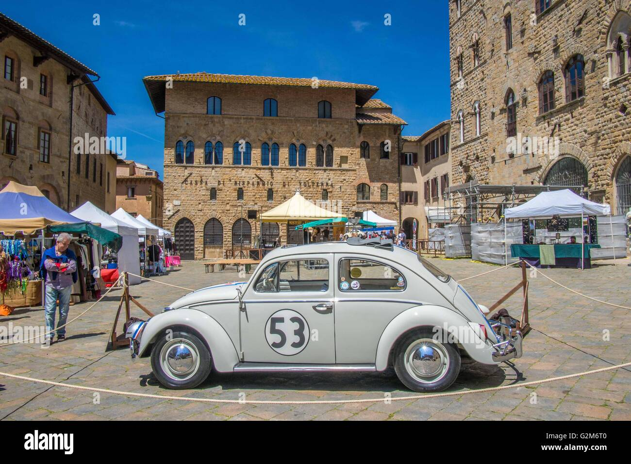 VW Beetle car in Piazza dei Priori, Volterra, a walled mountaintop town in Pisa province in the Tuscany region, - Stock Image