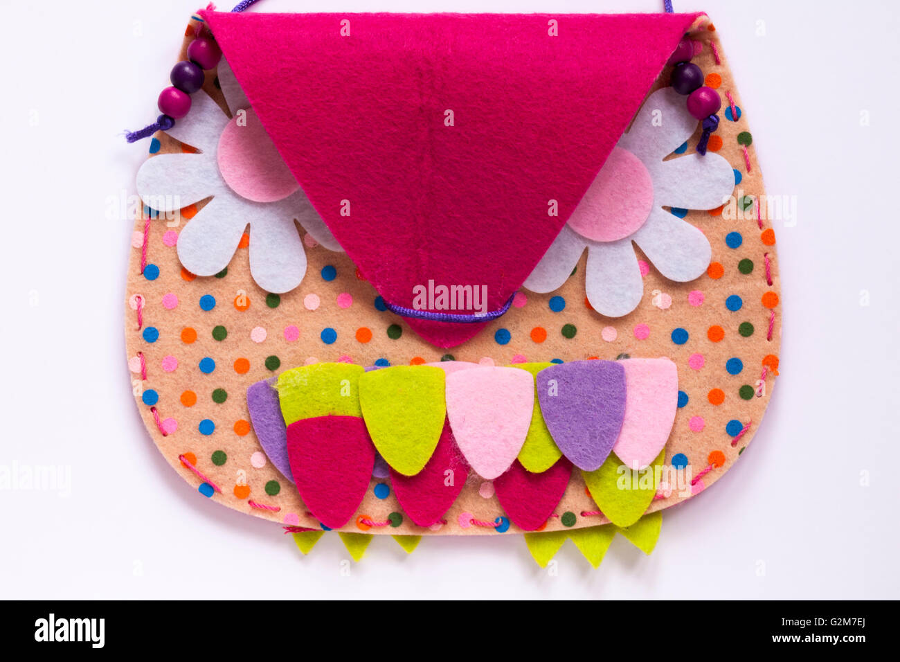 Girl's Pink felt bag with face on it set on white background - Stock Image