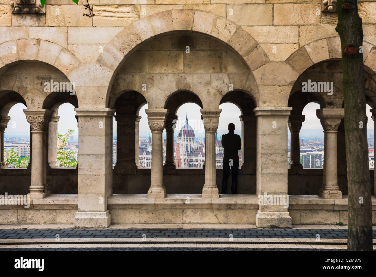 A tourist standing in a cloister in the Fishermens Bastion in Budapest looks over to the Parliament building on - Stock Image