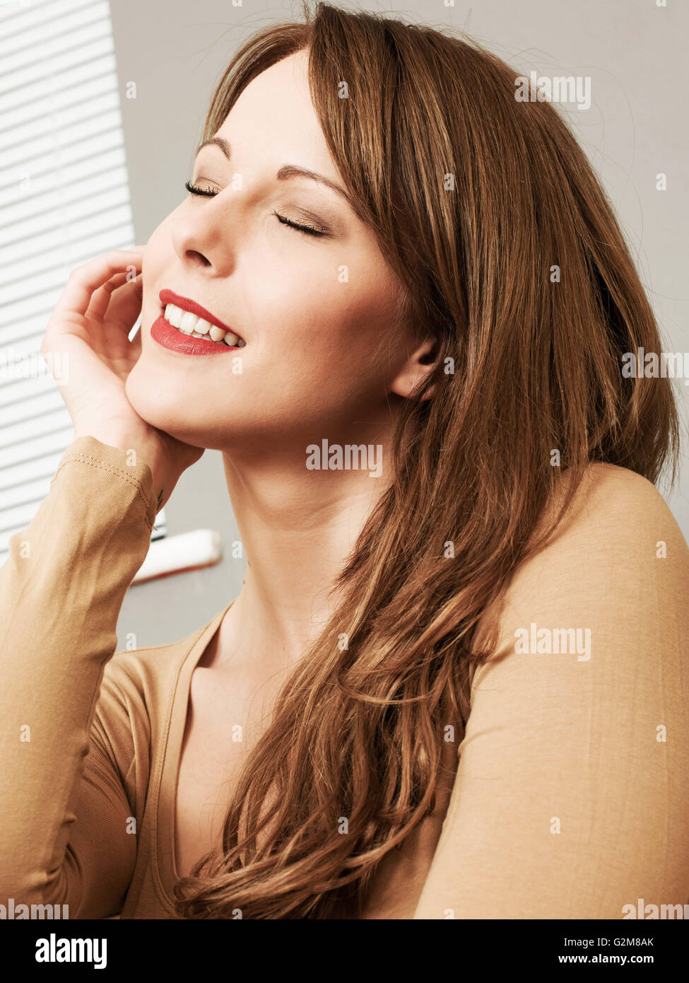 Portrait of a Happy Smiling Woman Remembering the Good Times Or Relieved a Personal Problem Has Been Resolved - Stock Image