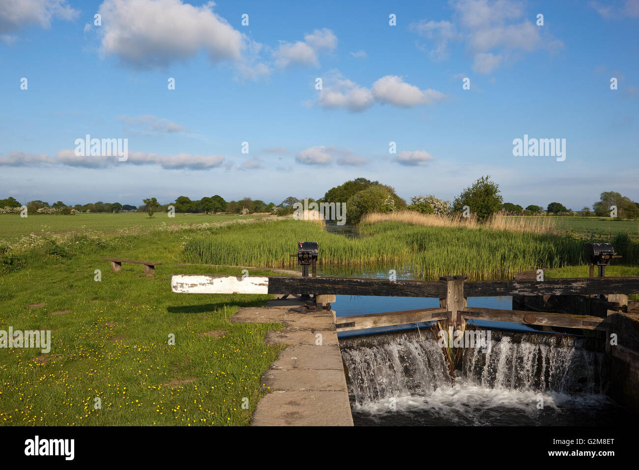 Water pouring through canal lock gates beside a rural towpath with benches and picnic area in an agricultural landscape - Stock Image