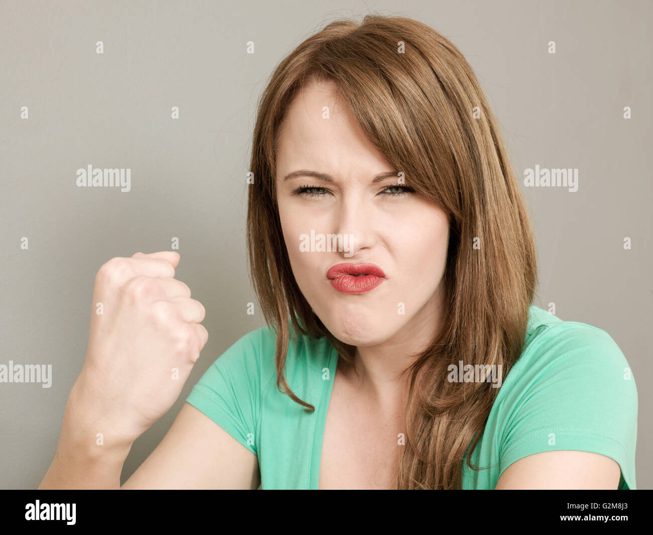 Portrait of an Angry Bad Tempered Young Caucasian Woman Frowning and Shaking Her Fist At The Camera - Stock Image