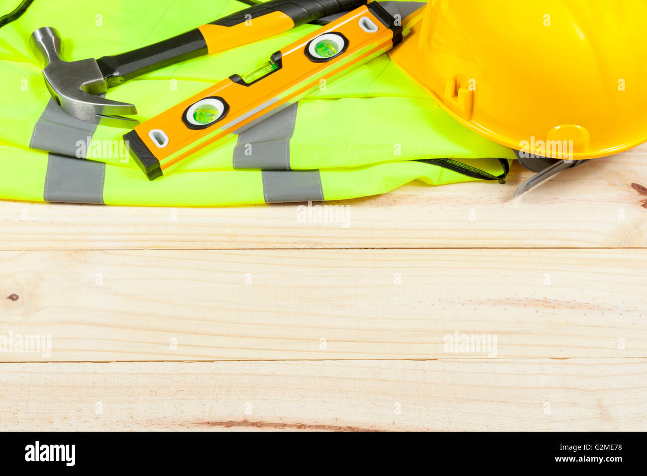 Claw hammer,spirit  level and yellow hard hat laying on a high visibility vest on a wooden background - Stock Image