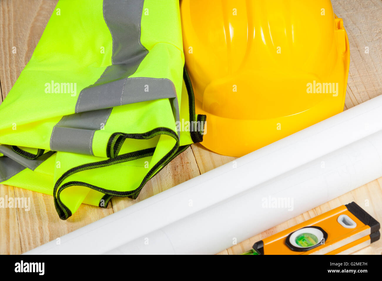 High visibility vest laying on a wooden floor with a yellow hard hat and a spirit level - Stock Image