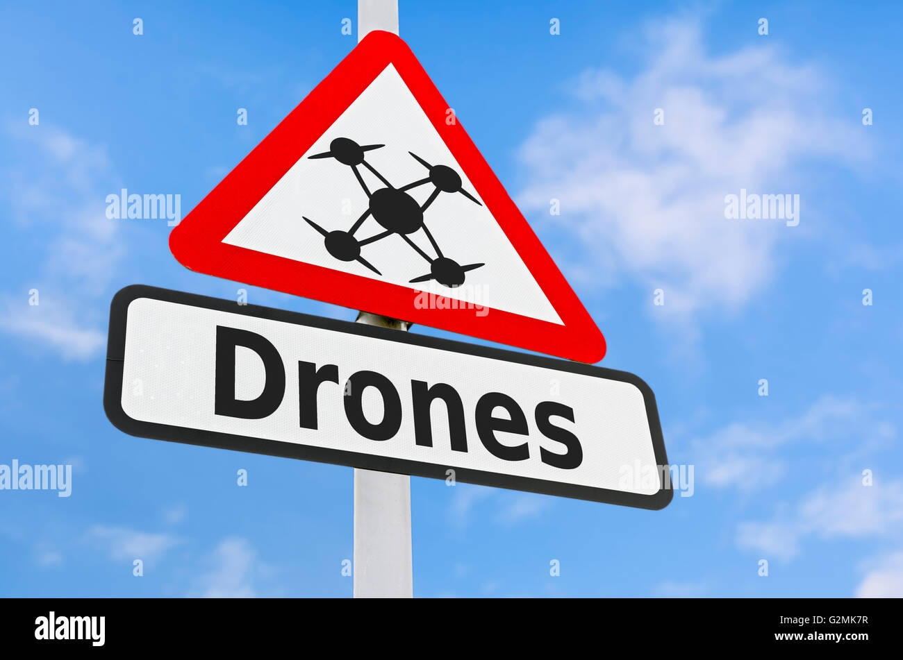 Drones triangular warning sign against blue sky. - Stock Image