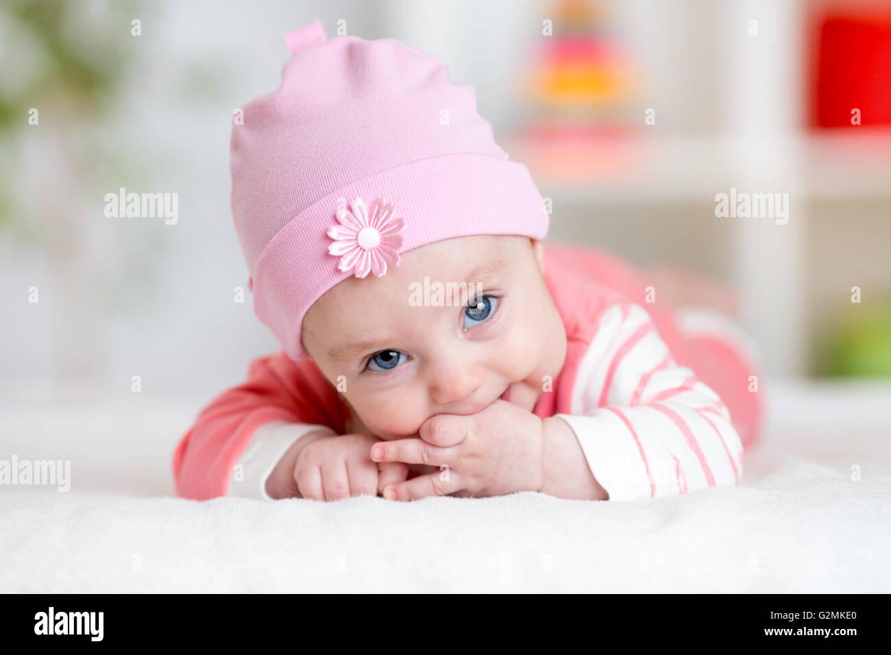 Baby teething sucks fingers. Infant kid lying in nursery - Stock Image