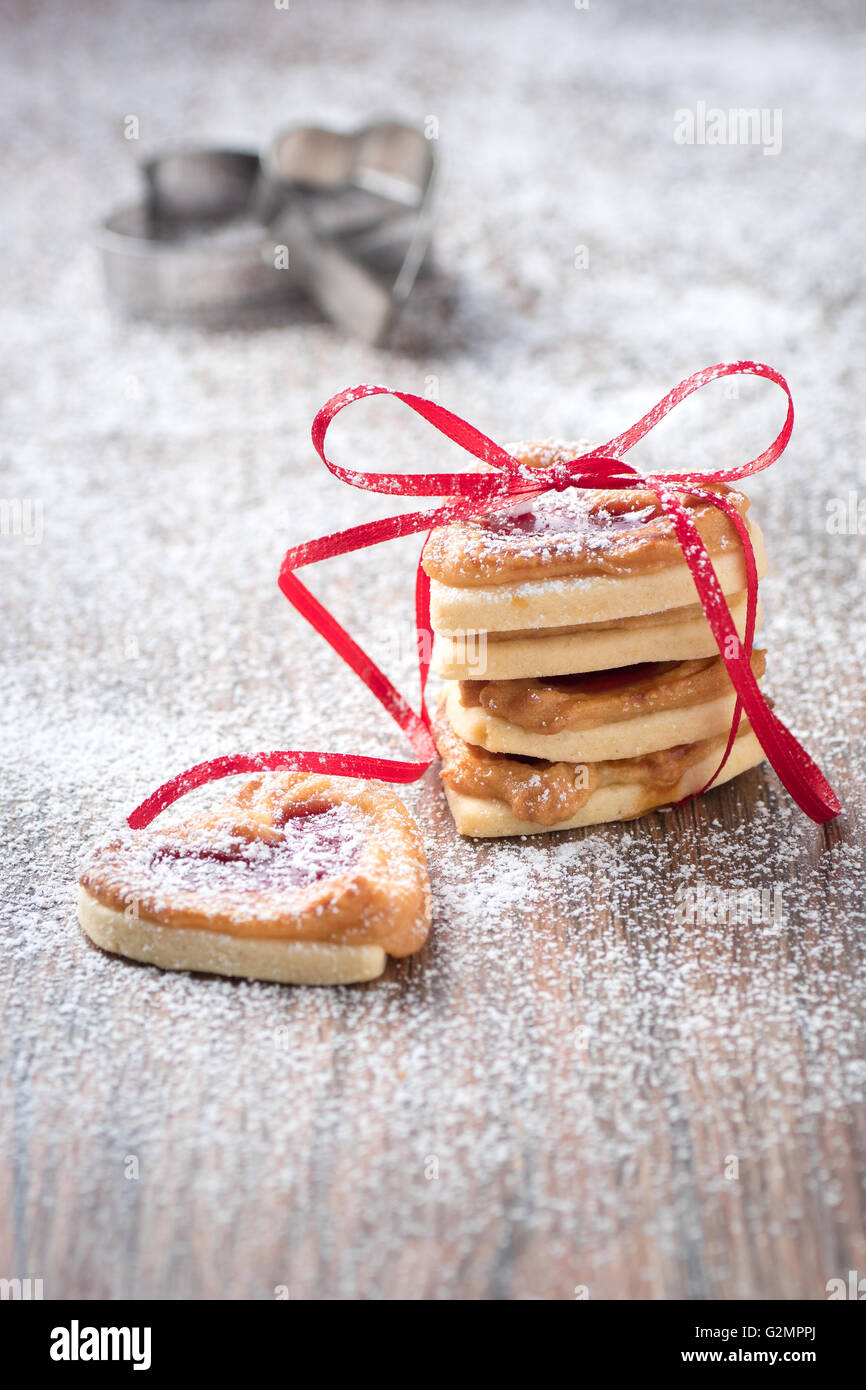Fresh cookies with icing sugar filled with jam an cookie cutter in the background. - Stock Image