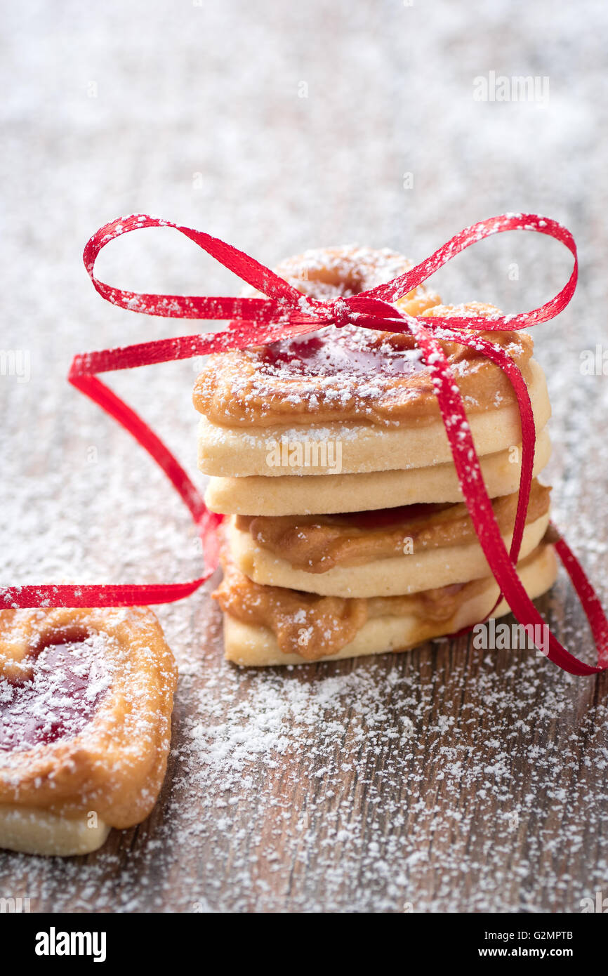 A pile of heart cookies on a rustic wooden table. You can use it for a greeting card or recipe. - Stock Image