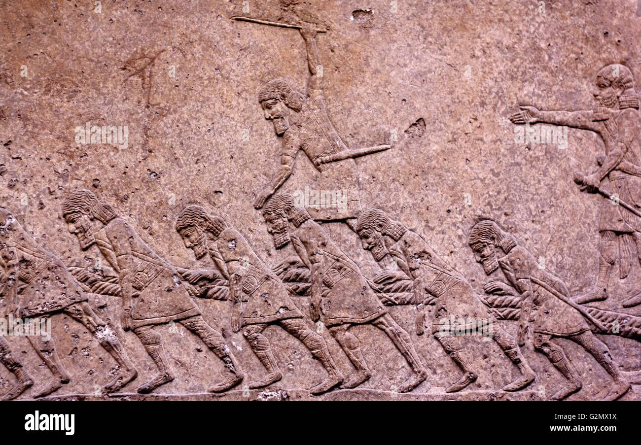Relief of Assyrian soldiers carrying away captured gods - Stock Image