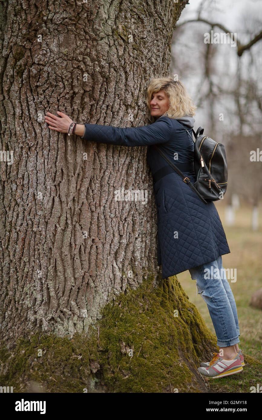 Beautiful blonde girl is hugging tree Stock Photo