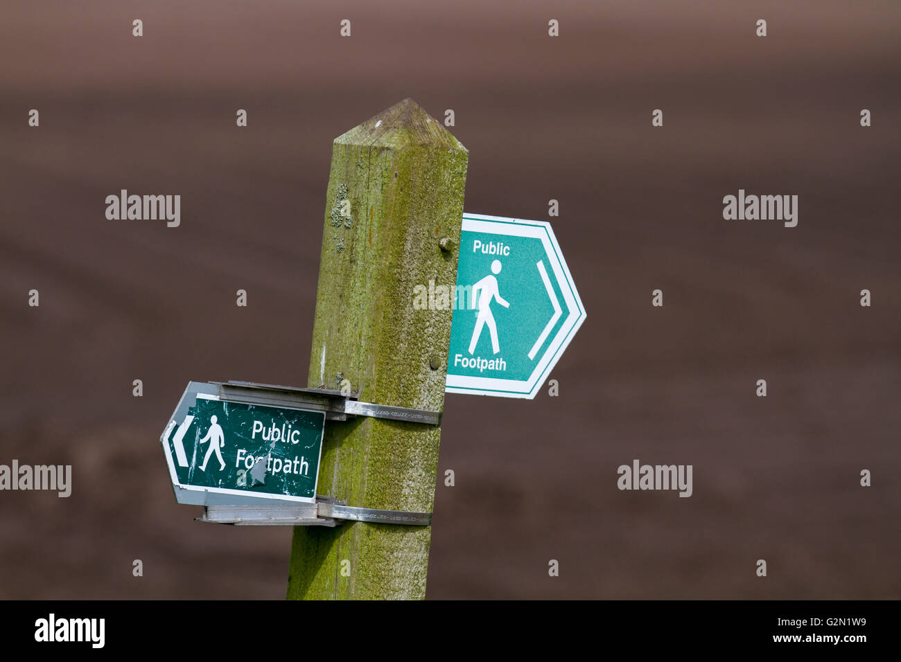 Two different waymarkers indicating Public footpath route signs across farmland in Burscough, Lancashire, UK - Stock Image