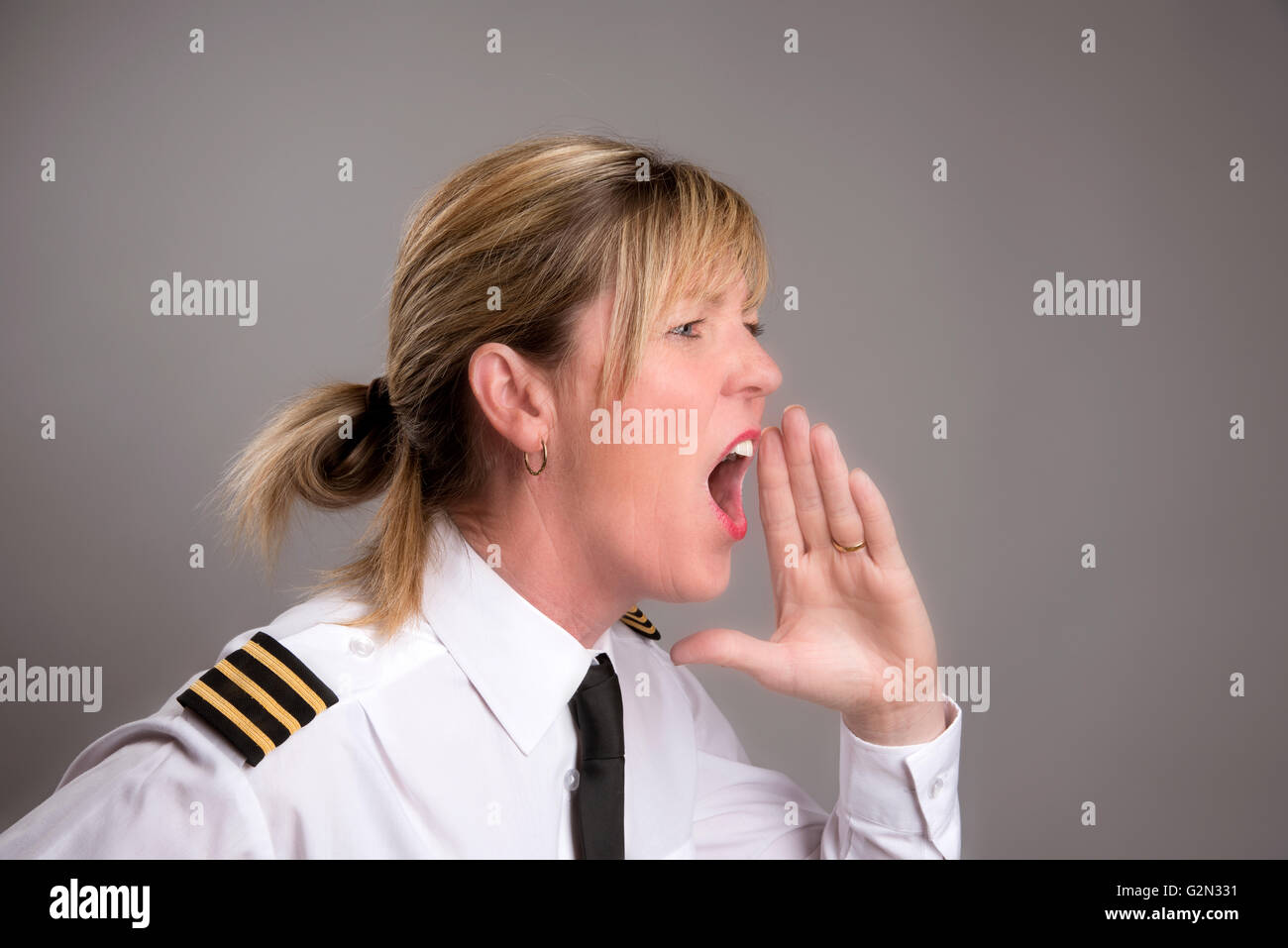 OFFICER SHOUTS AN ORDER  Portrait of a female uniformed officer shouting and order - Stock Image