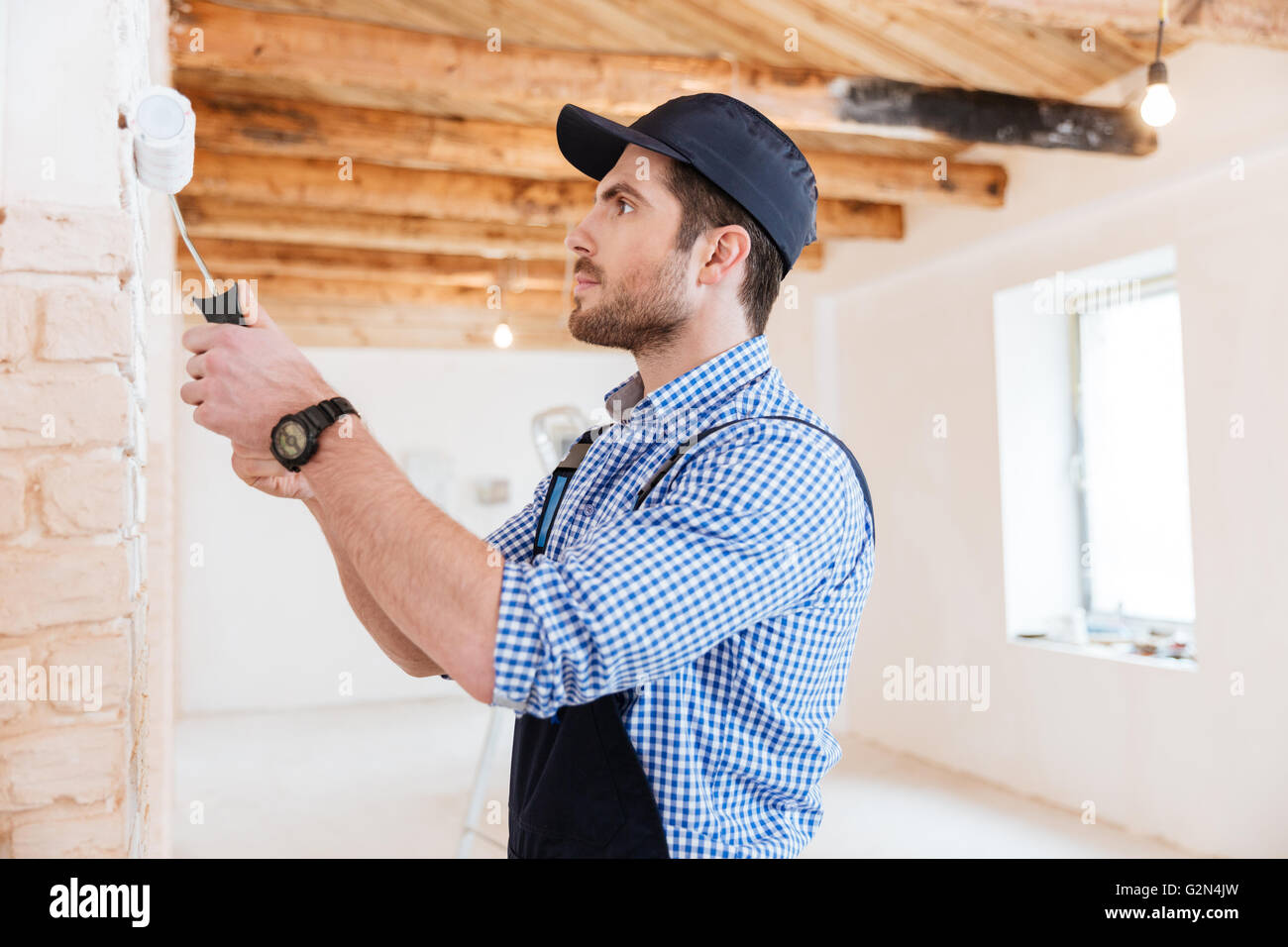Handsome young builder working with a paint roller indoors - Stock Image