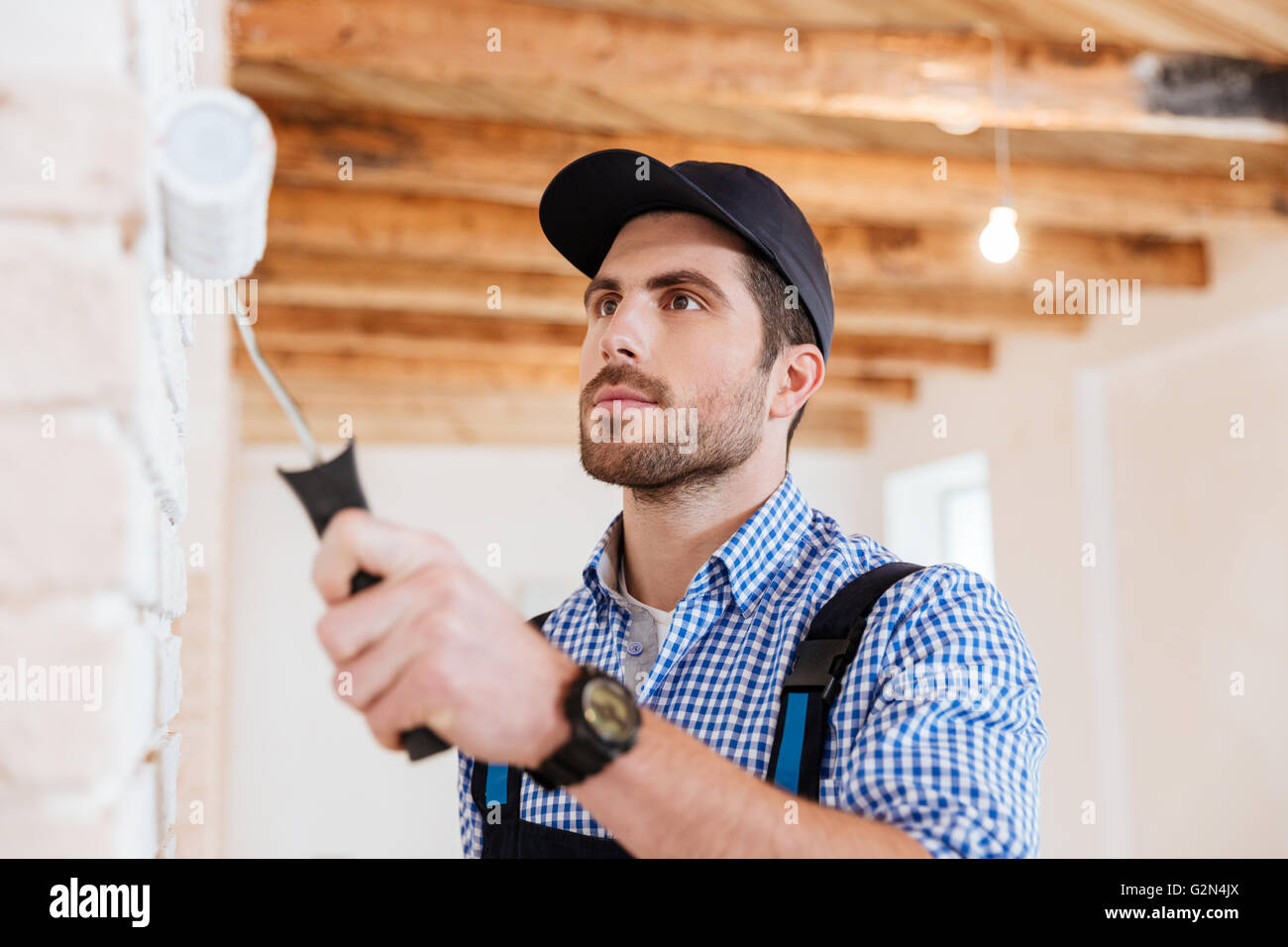 Close-up portrait of a builder worker decorator painting wall indoors - Stock Image