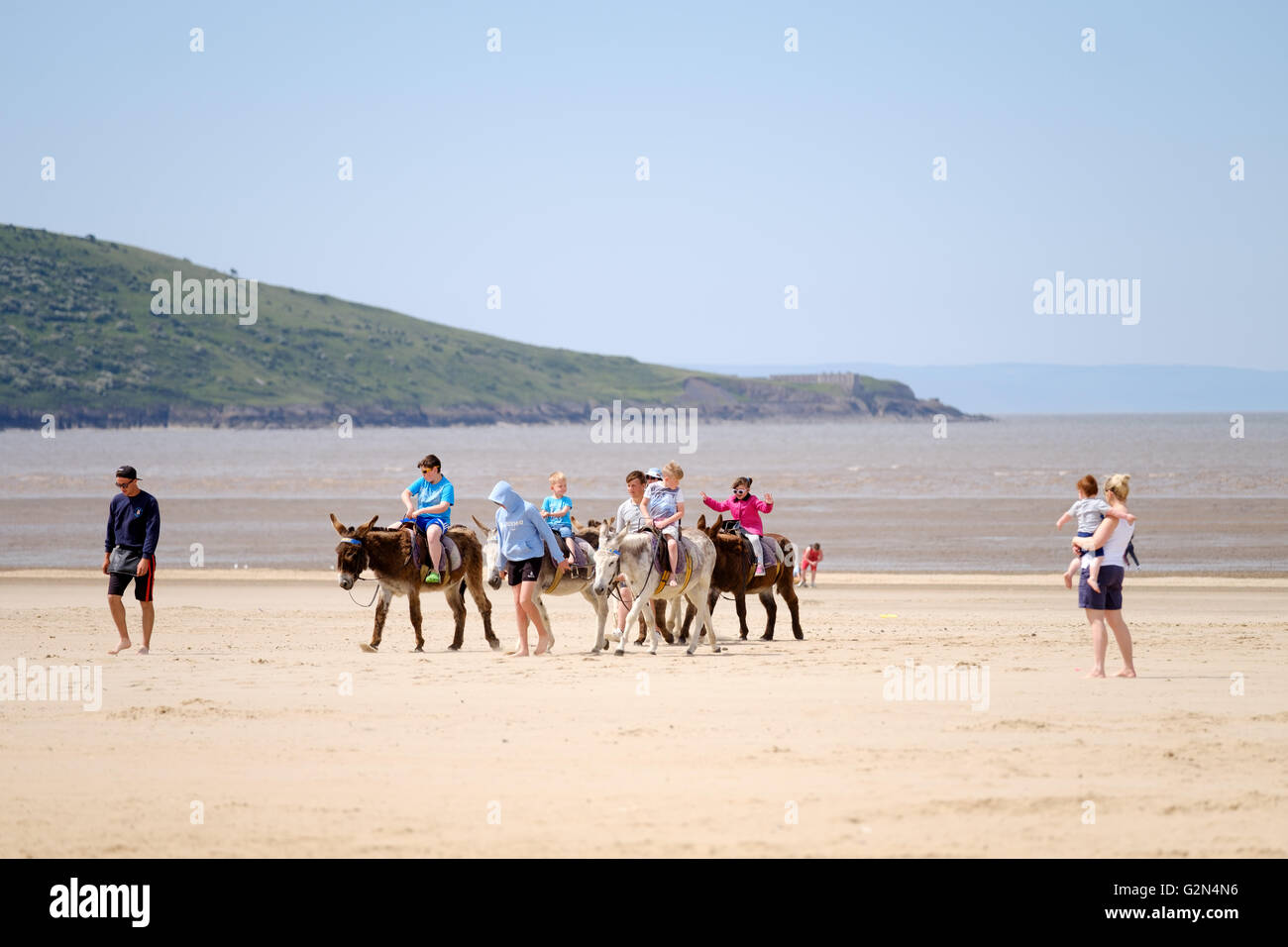 A group of children riding along a beach on seaside donkeys whilst a mother and child watch them Stock Photo