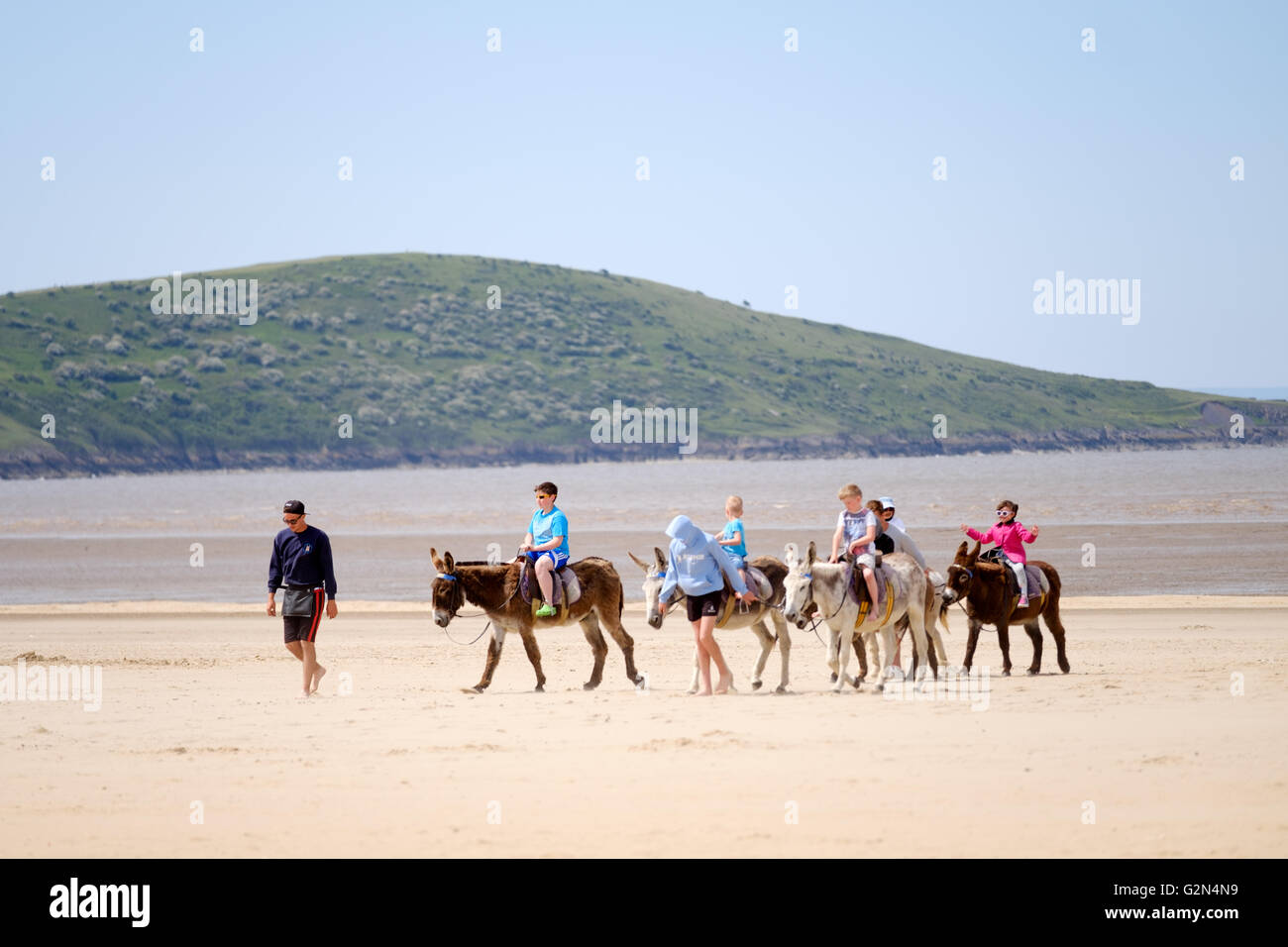 A group of children riding along a beach on seaside donkeys Stock Photo