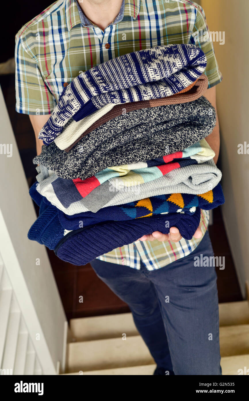 closeup of a young man wearing a short sleeved shirt carrying a pile of different folded sweaters - Stock Image
