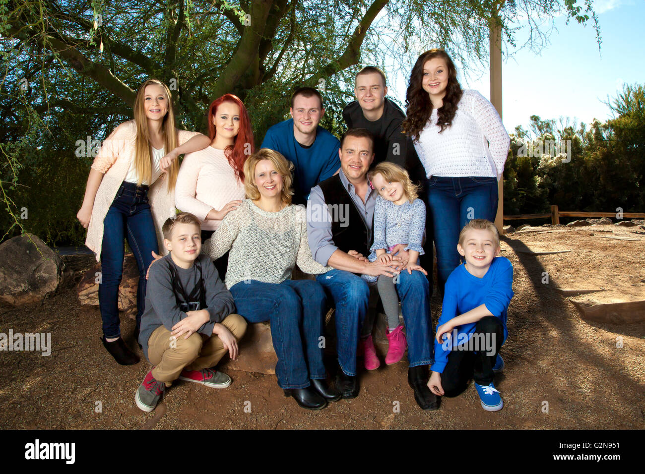 Portrait of a large family under a mesquite tree.  They are close and connected. - Stock Image