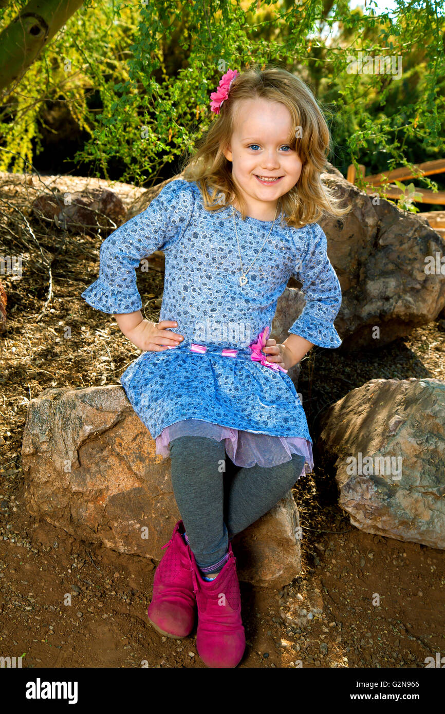 A very cute little girl with blond hair and blue eyes poses with her hands on her hips as she leans slightly to - Stock Image
