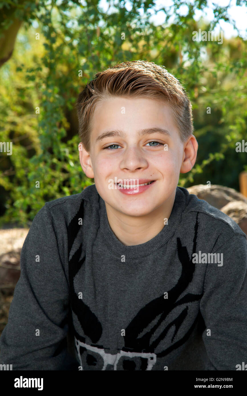 Portrait of a blond, tween boy smiling at the camera outdoors. - Stock Image