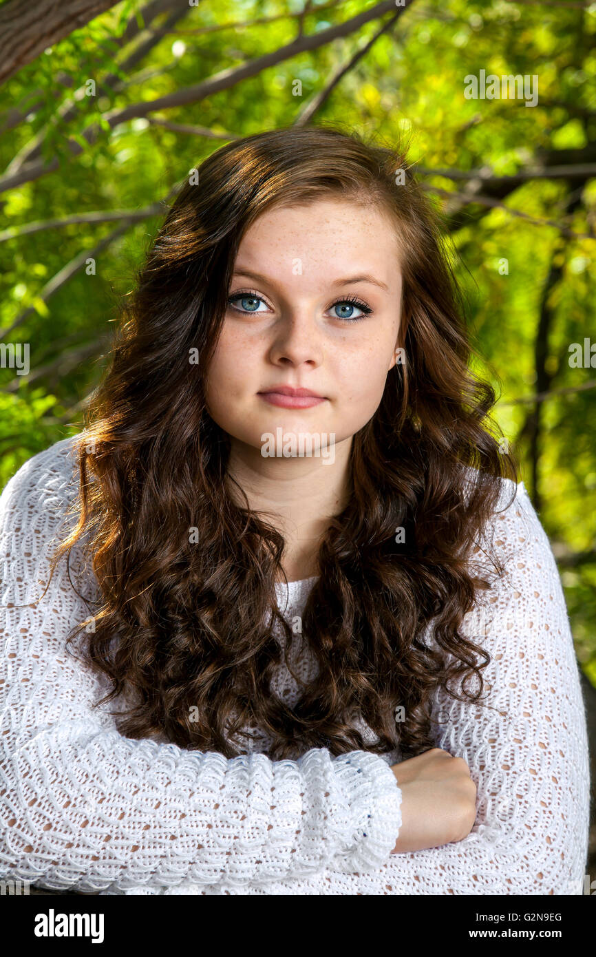 Portrait of a solemn, teenage girl.  She stares directly into the lens with an almost blank, but intriguing expression. - Stock Image