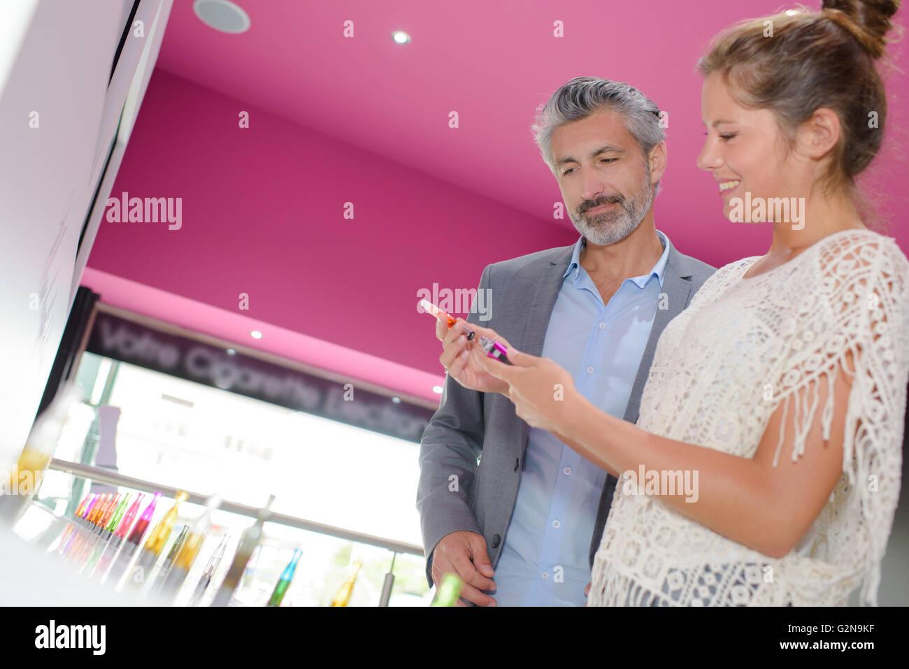Shop assistant showing vaporiser to customer - Stock Image