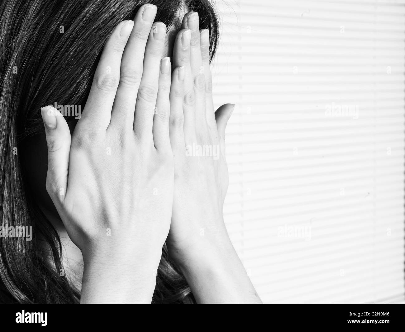 Black and White Portrait of a Young Woman Covering Her Face in Shame or Embarrassment - Stock Image