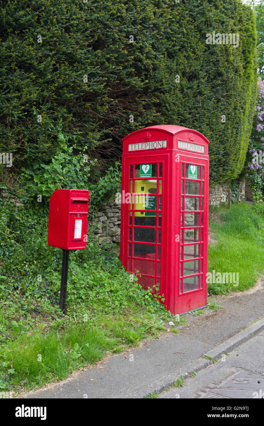 Red post office letterbox  next to a red telephone kiosk containing a defibrillator: in the village of Little Addington, - Stock Image