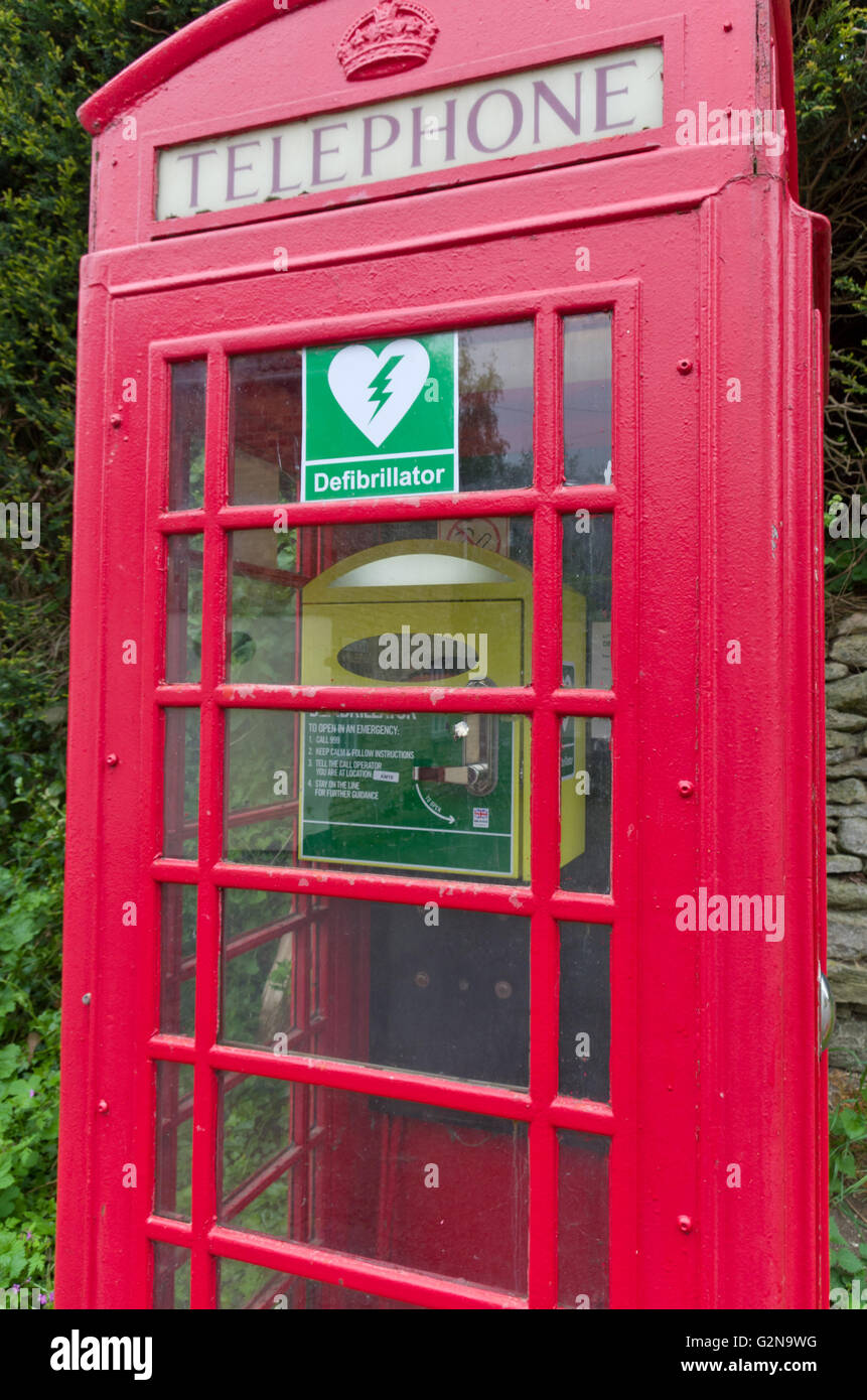 Red telephone kiosk with a defibrillator installed; in the village of Little Addington, UK - Stock Image