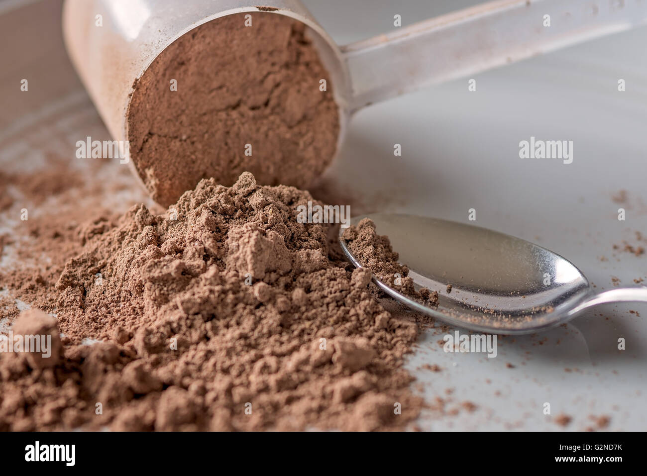 Chocolate meal protein powder spilling from a scoop next to a spoon - Stock Image