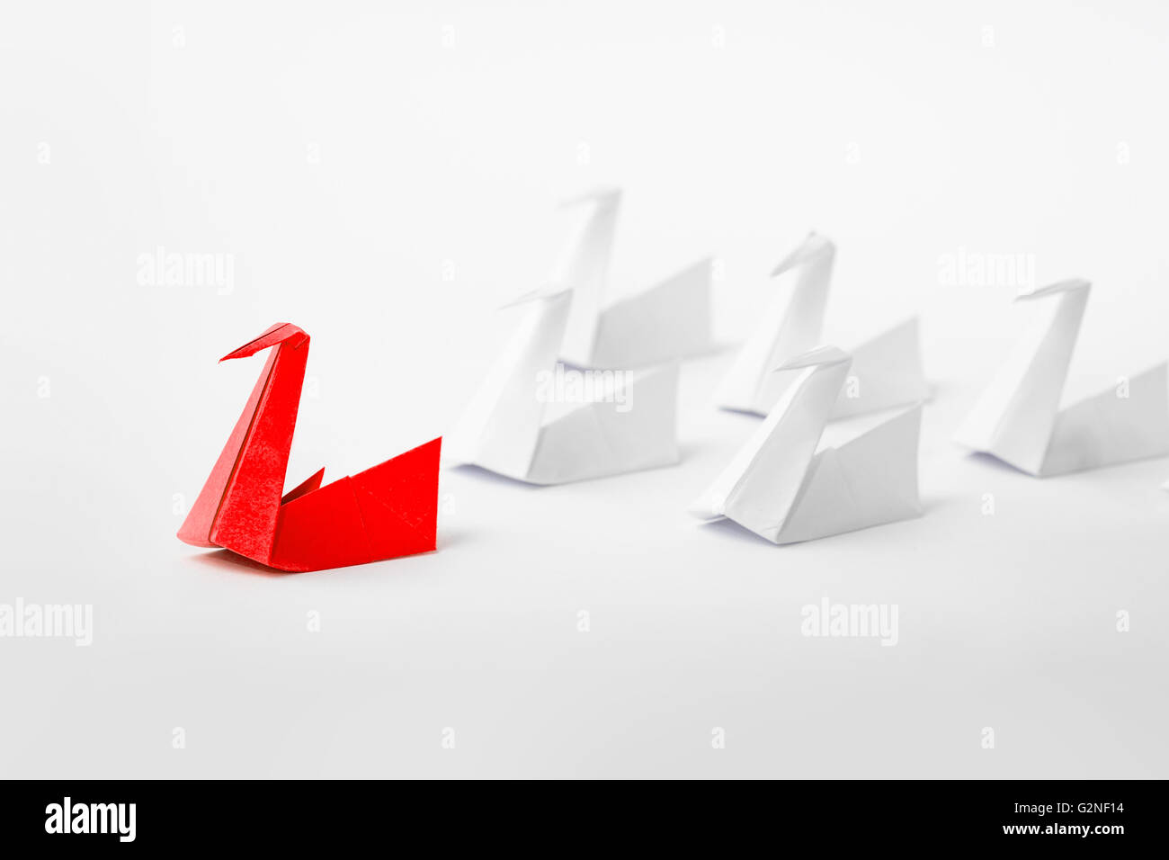 Leadership concept with origami paper bird leading among white. - Stock Image